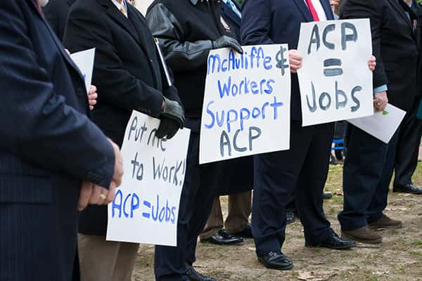 Businessmen Holding ACP Means Jobs Posters